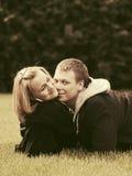 Jeunes couples heureux dans l'amour se trouvant sur l'herbe extérieure Photographie stock