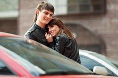 Jeunes couples heureux dans l'amour sur le stationnement de voiture Photographie stock libre de droits