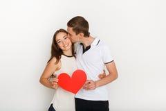 Jeunes couples heureux dans l'amour tenant le coeur de papier rouge Photos stock