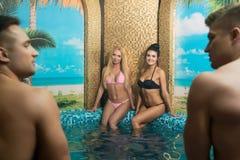 Jeunes couples heureux dans la piscine dans le sauna Photographie stock libre de droits