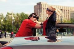 Jeunes couples heureux dans la voiture convertible Images stock