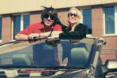 Jeunes couples heureux dans la voiture convertible Photos stock