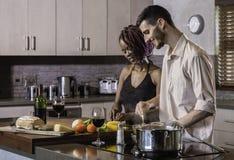 Jeunes couples heureux de métis faisant cuire le dîner dans la cuisine Images libres de droits
