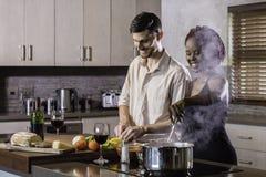 Jeunes couples heureux de métis faisant cuire le dîner dans la cuisine Photographie stock