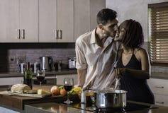 Jeunes couples heureux de métis faisant cuire le dîner dans la cuisine Image stock
