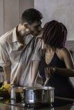 Jeunes couples heureux de métis faisant cuire le dîner dans la cuisine Photos libres de droits