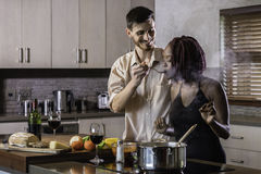 Jeunes couples heureux de métis faisant cuire le dîner dans la cuisine Photo stock