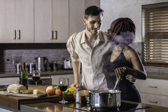 Jeunes couples heureux de métis faisant cuire le dîner dans la cuisine Photos stock