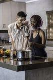 Jeunes couples heureux de métis faisant cuire le dîner dans la cuisine Images stock