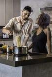 Jeunes couples heureux de métis faisant cuire le dîner dans la cuisine Image libre de droits