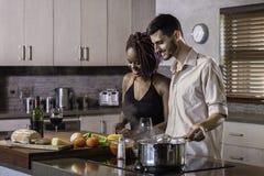 Jeunes couples heureux de métis faisant cuire le dîner préparant la nourriture dans la cuisine Images libres de droits