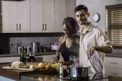 Jeunes couples heureux de métis faisant cuire le dîner préparant la nourriture dans la cuisine Photo stock