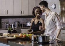 Jeunes couples heureux de métis faisant cuire le dîner préparant la nourriture dans la cuisine Photos libres de droits