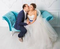 Jeunes couples heureux de mariage posant dans le studio Image stock