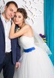 Jeunes couples heureux de mariage posant dans le studio blanc Photo stock