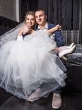 Jeunes couples heureux de mariage posant dans le studio blanc Photographie stock libre de droits