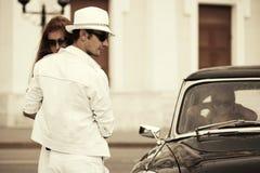Jeunes couples heureux de mode dans l'amour à côté de la rétro voiture Photographie stock libre de droits