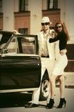 Jeunes couples heureux de mode dans l'amour à côté de la voiture de vintage Photographie stock