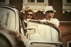 Jeunes couples heureux de mode dans l'amour à côté de la voiture de vintage Photo libre de droits