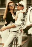 Jeunes couples heureux de mode dans l'amour à côté de la voiture de vintage Image stock