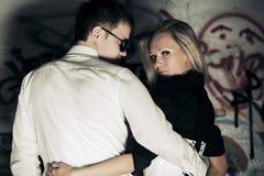 Jeunes couples heureux de mode dans l'amour au mur sale Photographie stock libre de droits