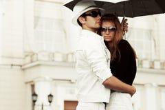 Jeunes couples heureux de mode dans l'amour avec le parapluie Image libre de droits