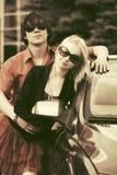 Jeunes couples heureux de mode dans l'amour près d'une nouvelle voiture Image stock