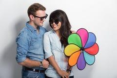 Jeunes couples heureux de Multiculture posant avec le moulin à vent Images libres de droits
