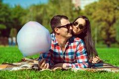 Jeunes couples heureux de sourire aimants dans des lunettes de soleil se trouvant sur la pelouse verte Images libres de droits
