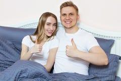 Jeunes couples heureux de sourire se situant dans le lit et l'exposition comme le signe Concept de la famille affectueux image stock