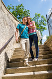 Jeunes couples heureux descendant le sourire d'escaliers Photographie stock