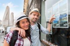 Jeunes couples heureux devant l'agence de voyages images stock