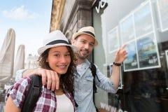 Jeunes couples heureux devant l'agence de voyages photos stock