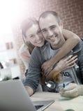 Jeunes couples heureux devant l'ordinateur portable Image stock