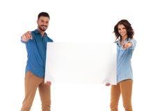 Jeunes couples heureux dirigeant des doigts tout en tenant le grand verrat vide Photos libres de droits