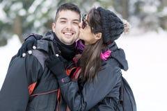 Jeunes couples heureux embrassant dans la montagne d'hiver Photo stock