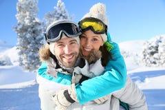 Jeunes couples heureux embrassant sur les pentes Photographie stock
