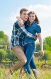 Jeunes couples heureux en étreindre d'amusement et ciel bleu Photographie stock libre de droits