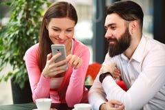 Jeunes couples heureux en café examinant un téléphone portable Images stock