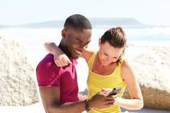 Jeunes couples heureux ensemble à la plage utilisant le téléphone portable image stock