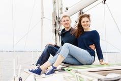 Jeunes couples heureux et beaux se reposant sur la plate-forme et ayant un aller Images stock