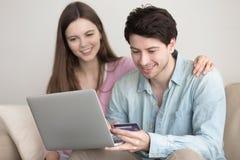 Jeunes couples heureux faisant des emplettes en ligne par l'intermédiaire de l'ordinateur portable avec la carte de crédit Photos stock