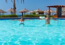 Jeunes couples heureux faisant la forme physique d'aqua dans la piscine Photos stock