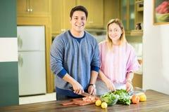Jeunes couples heureux faisant la salade végétale photographie stock libre de droits