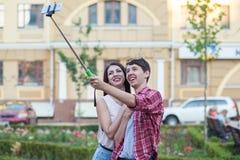Jeunes couples heureux faisant le selfie par le téléphone portable intelligent dans la ville Photos libres de droits