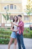 Jeunes couples heureux faisant le selfie par le téléphone portable intelligent dans la ville Photographie stock