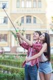 Jeunes couples heureux faisant le selfie par le téléphone portable intelligent dans la ville Photographie stock libre de droits