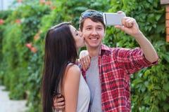 Jeunes couples heureux faisant le selfie par le téléphone portable intelligent dans la ville Photo libre de droits