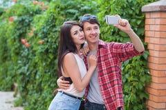 Jeunes couples heureux faisant le selfie par le téléphone portable intelligent dans la ville Images libres de droits