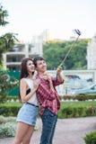 Jeunes couples heureux faisant le selfie par le téléphone portable intelligent dans la ville Photo stock